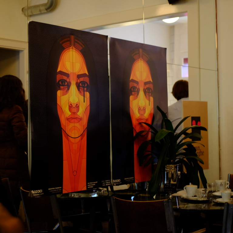 two posters of a woman in café noir