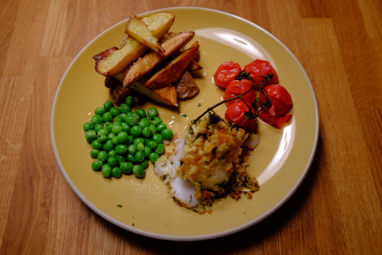 Plate with fish, chips, peas and tomatoes