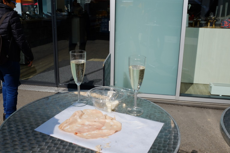 Table with two glasses of prosecco and some dried meat